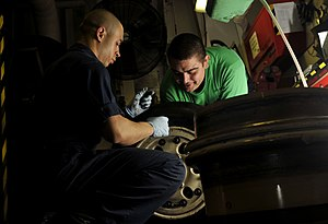 US Navy 120112-N-ZI635-110 Sailors perform maintenance on the tire of an F-A-18 C Hornet.jpg