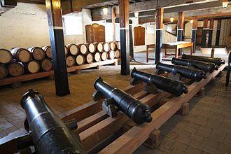 Upnor Castle - Display of gunpowder barrels and naval howitzers in the magazine block
