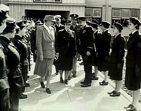 Two women and three men flanked by two lines of women in dark military uniforms