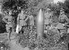 A group photograph of several men in uniform who are standing around an unexploded shell that is standing pointed-end up from the ground.