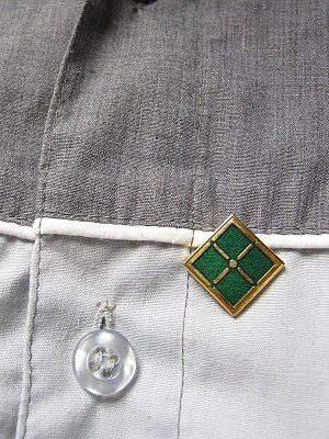 An ITIL Foundation Certificate pin on a shirt.