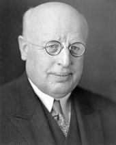 A photographic portrait of a balding white man with small round glasses