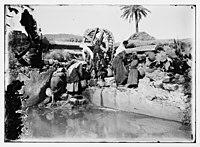 Women and children with jars getting water from stream next to irrigation wheel LOC matpc.06026.jpg