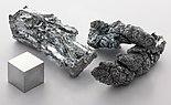 Um cristal de um metal prateado de cor, um cristal de um metal escuro e um cubo de metal de pé sobre uma superfície cinzento claro
