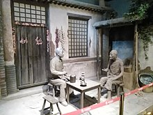 Model of a Chinese dwelling with clay models of two men sitting at a table in conversation