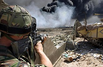 Battle of Basra (2003) - A British soldier covers sappers capping a burning oil well in Basra. 3 April 2003