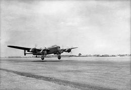 Four-engined, twin-finned military aircraft taking off
