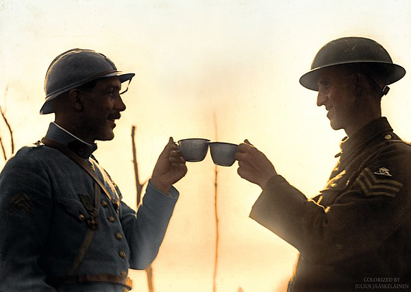 A French soldier and a sergeant British of the Royal Garrison Artillery toasting each other in French ration wine at Boezinge, 18th August 1917. (49038454518).jpg
