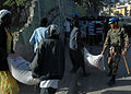 A United Nations peacekeeper from Jordan assists a Haitian woman carrying a 100-pound bag of rice outside Port-au-Prince, Haiti 100213-N-HX866-002.jpg