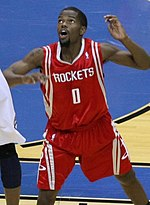 "A basketball player, wearing a red jersey with the word ""HOUSTON"" and the number 0 on the front, stands on a basketball court."