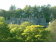 Peeping over the tops of trees in the foreground is a stone house with five gables of different sizes. More trees are in the background.