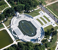 Aerial view of oval-shaped memorial with pond and white walkways