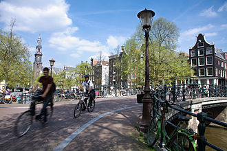 Police bicyclist crossing a bridge over the Prinsengracht Amsterdam - Bicycles - 1058.jpg