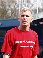 "A man with blonde hair who is wearing a red top, which reads ""Bobby Moore Fund""."
