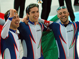 Head and torso photo of three smiling men, wearing glasses on their heads and blue and white jumpsuits with Italia written on the chest. The man in the middle is holding a big Italian flag behind him, while the other two are embracing him.