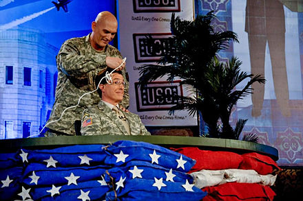 "Colbert receives an ""Army"" haircut, from Four-Star General Ray Odierno, during filming."