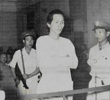 Dishevelled man dressed in white folds his arms as he stands in the dock. He is guarded by two soldiers, one with a machine gun. The courtroom is crowded.