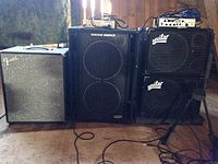 "A Fender bass cabinet, a Genz Benz bass cabinet, and two Aguilar cabinets are shown. The Genz Benz and Aguilar cabinets each have amplifier ""heads"" sitting on top."
