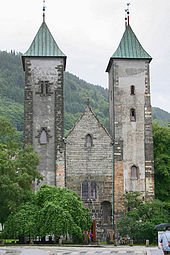 Stone  Romanesque church with two  towers and a  lower, pitched roof entrance hall between them. The towers have slightly curved  bronze roofs.