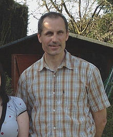 Man with oval head and crew-cut dark hair stands outdoors wearing large-checked brown and white shirt