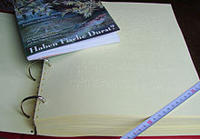 """In an open ring binder, a pack about two fingers thick with Braille printed paper.  A centimeter ruler was placed across the lower right corner to compare sizes;  the paper is about DIN A4 size.  On the upper half of the paper is a narrow paperback about half the size (DIN A5) with the title """"Do fish thirst?"""""""