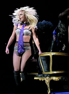 Image of a blond female performer. She has a headset around her hand and is wearing sparkly silver and black lingerie, fishnet stockings and knee-high black boots, she stands in front of a black and golden couch.