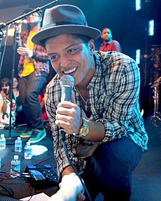 Bruno Mars down on one knee at the front of a stage, singing into a microphone, with someone in the audience holding his forearm. He is wearing black pants, a plaid button-up shirt, and a gray fedora.