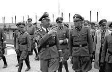 Ryhmä natsiupseereja, mukaan lukien Heinrich Himmler, Franz Ziereis, Karl Wolff ja August Eigruber, näyttivät kävelevän ja puhumassa leirin läpi, yhden mökin taustalla.