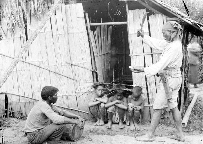 COLLECTIE TROPENMUSEUM Een shamaan op Zuid-Boeroe bezweert boze geesten de kinderen te verlaten waarbij hij een geldstuk en een sirihnoot offert TMnr 10001031