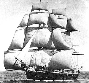 A sailing ship running before the wind, coming toward the observer at an oblique angle, with squaresails and studding sails set on the masts and a headsail set from the bowsprit