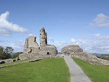 Grey stone ruins, with tall upstanding remains of tower, on a grassy hill, pictured against blue sky.