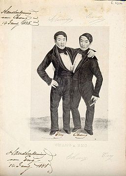 Chang and Eng the Siamese twins, one holding a book. Lithograph Wellcome V0007364