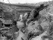 Soldier on guard armed with a rifle wearing a Brodie helmet, three other men are asleep in the bottom of the trench