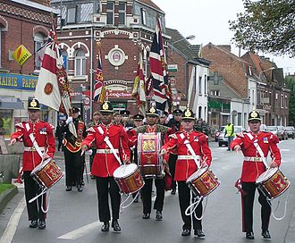 Red coat (military uniform) - The drums platoon of the Duke of Wellington's Regiment (West Riding), leading the regiment, with its colours, through Erquinghem-Lys, France to the Town Hall to receive the keys to the town in 2005.