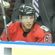 An ice hockey player sitting on the bench. He is wearing a black helmet with a visor and a red jersey with the number 61 on the sleeves.
