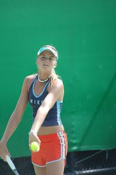 Daniela Hanutchova wearing a black top and red shorts, just about the serve the ball
