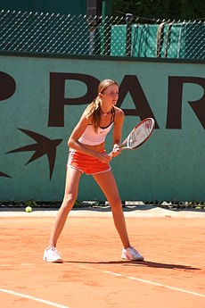 Daniela Hantuchova in a white top and red shorts with white trim, waiting to receive a serve on a red clay court