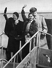 La famille MacArthur se trouvant au sommet de la rampe d'accès à un avion de passagers. Douglas MacArthur se tient à l'arrière de sa femme Jean et de son fils Arthur qui saluent.
