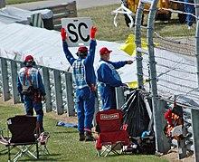 Due commissari di pista segnalano la bandiera gialla e un cartello con la sigla