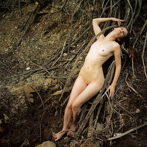 Female nude next to tree roots