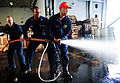 From left, U.S. Navy Machinist's Mate 3rd Class Steven Sanday, Electrician's Mate 2nd Class Brandon Osefoh and Chief Warrant Officer Kevin Davis practice hose-handling techniques during a damage control olympics 130610-N-XE109-152.jpg