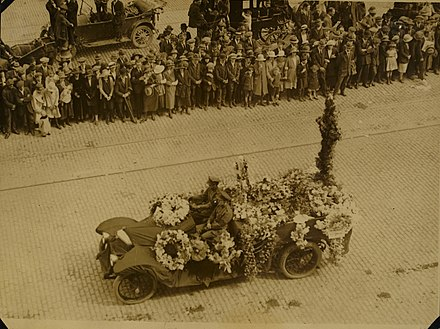 National Army soldiers drive a car laden with wreaths through the streets of Dublin towards Glasnevin Cemetery for the burial of Michael Collins (1922) Funeral of Michael Collins (9614214226).jpg