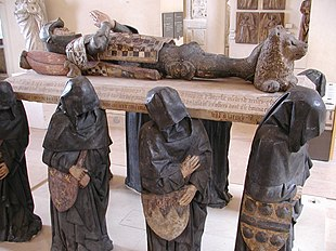 A large sculpture of six life-sized black-cloaked men, their faces obscured by their hoods, carrying a slab upon which lies the supine effigy of a knight, with hands folded together in prayer. His head rests on a pillow, and his feet on a small reclining lion.