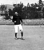 B&W photo of middleaged man standing on a pitch with a football