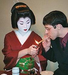 Une geisha accueillant un homme d'affaire américain dans le quartier de Gion à Kyōto au Japon (Photographie par Todd Laracuenta, 2003).