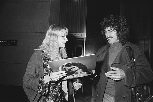Harrison leaving the Hilton Hotel in Amsterdam, and signing an album for a fan, February 1977 GeorgeHarrison1977.jpg