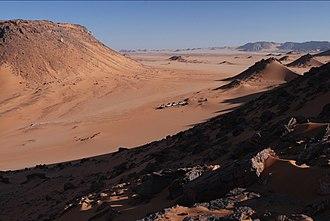 Gilf Kebir - A caravan of tourist 4x4s seen from atop a mesa in Gilf Kebir, Egypt.