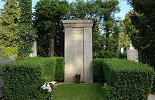 "A tall stone column bearing the words ""Gustav Mahler"", surrounded by a low green hedge, with a floral bloom in the foreground"