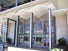 glass lobby with several columns in front holding a roof to shelter the doorway, with a tile mosaic of sports figures inside the lobby