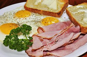 "Ham and eggs served with thinly-sliced ham and fried eggs prepared ""sunny side up"", served with toast"